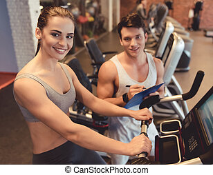 At the gym - Attractive young woman is smiling while working...