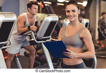At the gym - Attractive woman trainer is looking at camera...