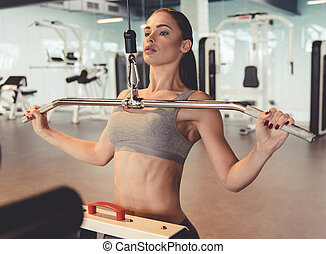 Woman at the gym - Attractive young woman is working out on...