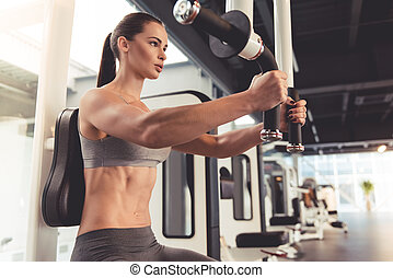 Woman at the gym - Beautiful young woman is working out on a...
