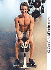 Man at the gym - Handsome young muscled man is looking at...
