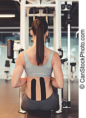 Woman at the gym - Back view of beautiful young woman...