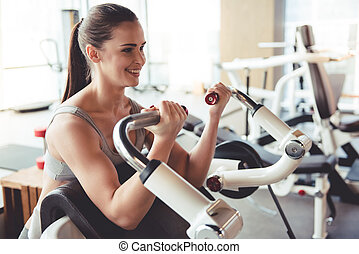 Woman at the gym - Beautiful young woman is smiling while...