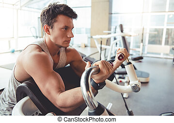 Man at the gym - Handsome young muscled man is working out...