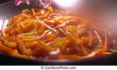 Adding red onion to sweet pepper pieces in a frying pan....