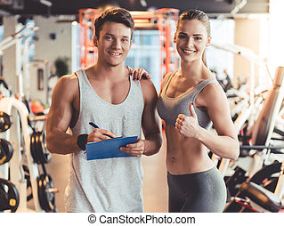 At the gym - Attractive young people are looking at camera...