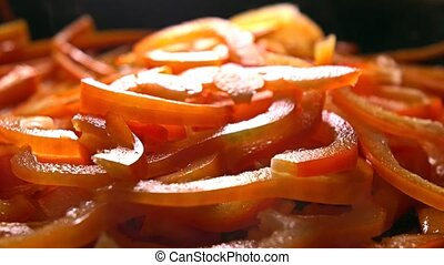 Adding green celery to cut sweet pepper in a frying pan. 4K close-up video