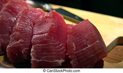 Cut tuna fillet pieces on wooden board. 4K close-up dolly...
