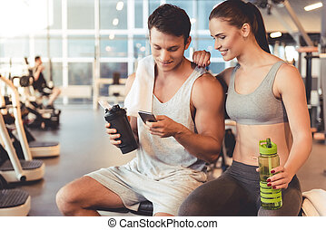 At the gym - Attractive young sports people are holding...