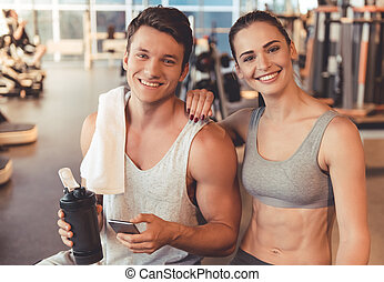 At the gym - Attractive young sports people are talking and...