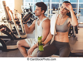 At the gym - Attractive young sports people are drinking...