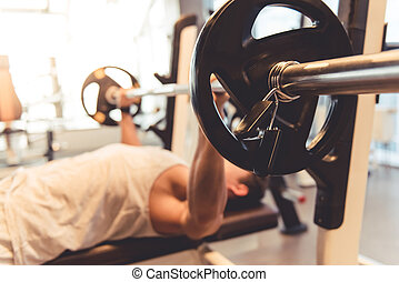 Man at the gym - Attractive young muscular man is lifting...