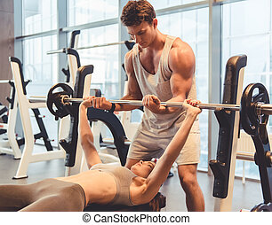 At the gym - Attractive young woman is lifting weight in...