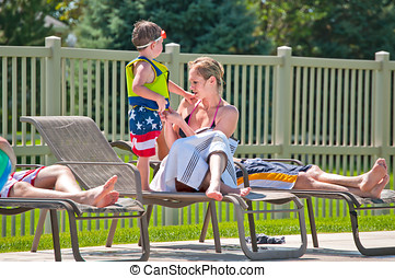 Young mother with son at swimming pool - Pretty woman in...