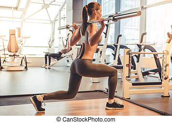 Woman at the gym - Attractive young woman is lifting weight...