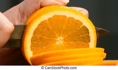 Close-up. Women's hands cut a juicy orange slices.