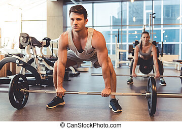 At the gym - Attractive young people are working out with...