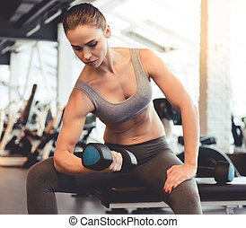 Woman at the gym - Attractive young woman is working out...