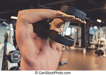 Man at the gym - Attractive young muscular man is working...