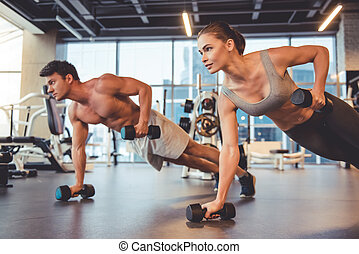 At the gym - Attractive young sports people are working out...
