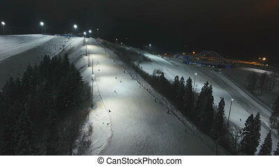 Ski resort at night. Aerial view. - Aerial view: Skiers and...
