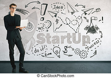 Start up concept - Young businessman using laptop in...