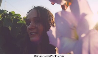 Young beautiful woman looks in flowers outdoor at sunset through the sun in slow motion with lense flare effects. 1920x1080
