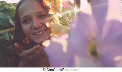 Young beautiful woman smiles and hides in flowers outdoor at...