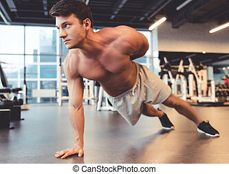 Man at the gym - Attractive young muscular man is doing...