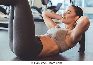 Woman at the gym - Attractive young woman is smiling while...