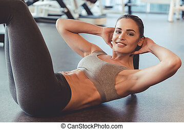 Woman at the gym - Attractive young woman is looking at...