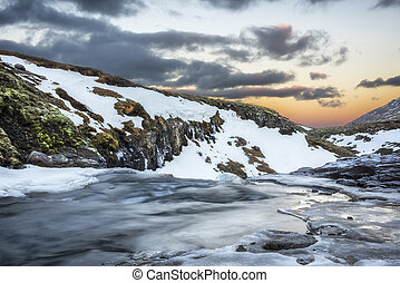 An icy river at sunrise in Iceland - A cold snowy river in...