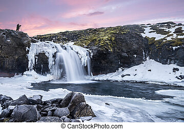 An icy waterfall during sunrise in Iceland - A cold snowy...