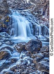 Waterfall in Iceland - A waterfall in Iceland cascades down...