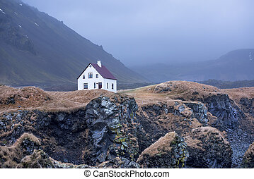 House on ocean cliff in Iceland - A small white building...