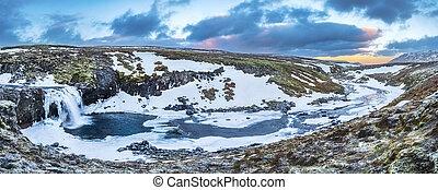 An icy waterfall panorama during sunrise in Iceland - A cold...