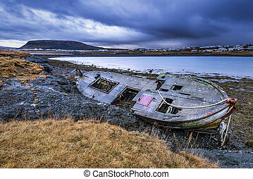 An old abandoned fishing vessel from the early 1900's rests on a remote beach as it rots