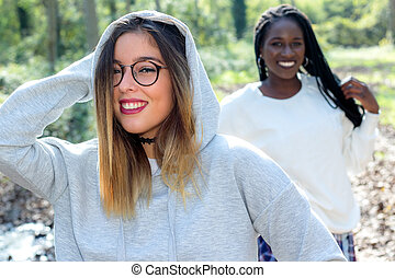 Cute teen girl with african friend in background.
