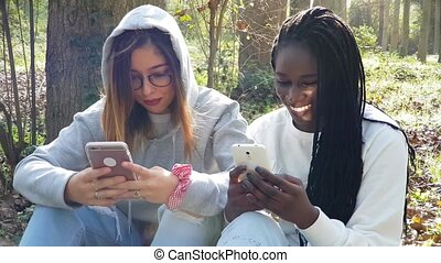 Two diverse teen girls having fun together on smart phones....