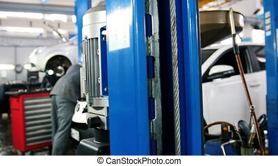 Mechanic in car service fixing and repairing detail of automobile, slider