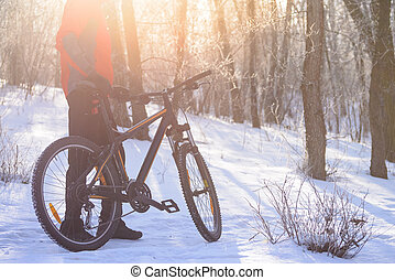 Mountain Biker with his Bike on the Snowy Trail in the Beautiful Winter Forest Lit by Sun