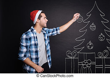 Positive young man decorating a Christmas tree.