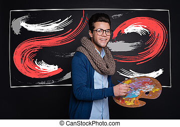 Happy stylish man holding palette and painting. - Creating...