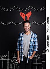 Joyful young man wearing Christmas reindeer antlers. -...