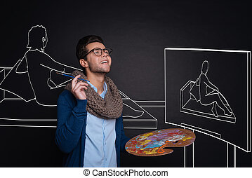 Inspired handsome man holding palette and painting. -...