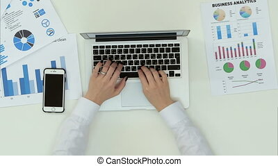 Woman's hands typing on laptop at office desk with...