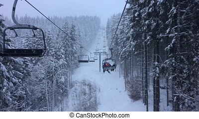 People ride on the chair lift among the trees covered with...