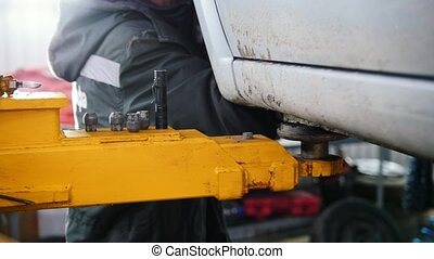 Car in auto service lifting for repairing, slider,close up
