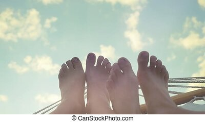 Young couple feet rest in hammock on the sky background in...