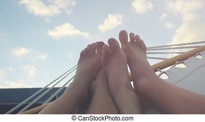 View on young couple feet rest in hammock on the sky...